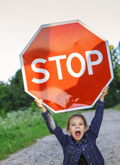 "little girl holding a red sign ""STOP"""