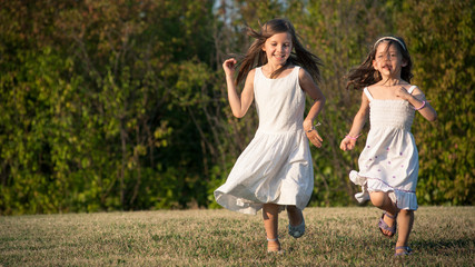 Young sisters running together in the park.