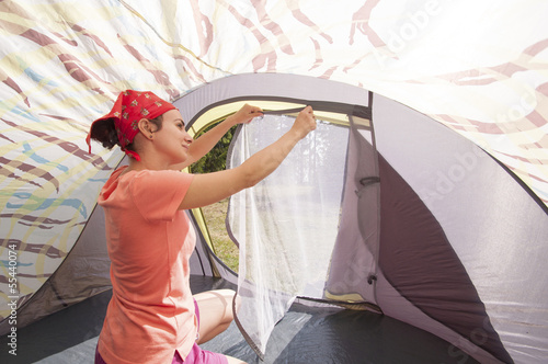 Young woman arranging the tent