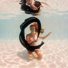 Underwater woman fashion portrait with black veil in swimming po