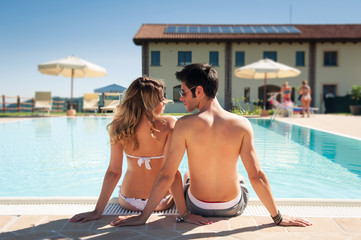 Young couple from behind in a swimming pool.