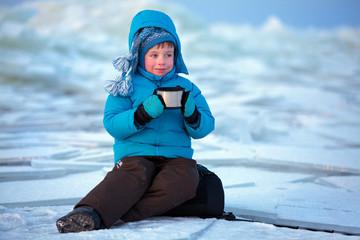 Cute little boy drinking hot tea in winter beach