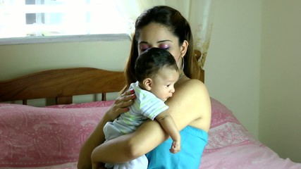 mother holding drooling baby over shoulder