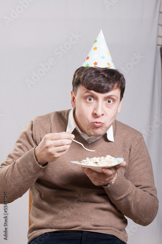 Man wearing a party hat eats salad
