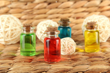 Bottles with colored liquids on  wicker wooden background