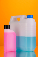 Blue and pink liquids for car in canisters on orange background