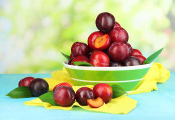 Ripe plums in bowl on wooden table on natural background