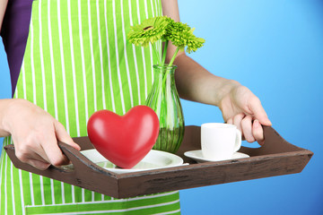 Woman in green apron holding wooden tray with breakfast,