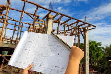 architecture drawings in hand on house building background with