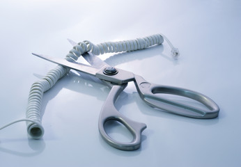 Telephone cord being cut by scissors