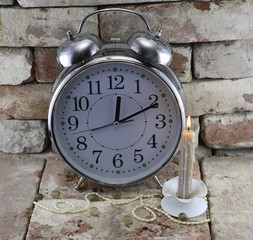 Old-fashioned clock with burning candle