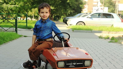 Cute three year old boy posing sitting on a toy car