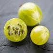 Ripe green gooseberries over dark wooden background, macro shot