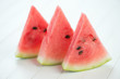Three slices of ripe watermelon over white wooden boards