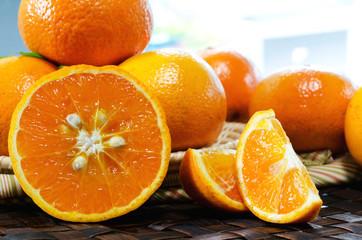 tangerines with leaves in a beautiful basket, on wickerwork tabl