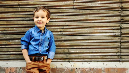 Cute three year old boy posing against wooden house wall