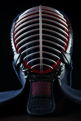 Vertical shot of kendo helmet over dark background, close-up
