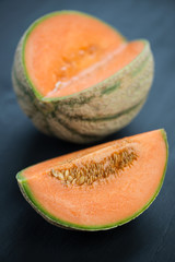 Vertical shot of ripe cantaloupe, dark wooden background