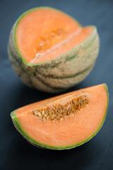 Vertical shot of ripe cantaloupe, dark wooden background