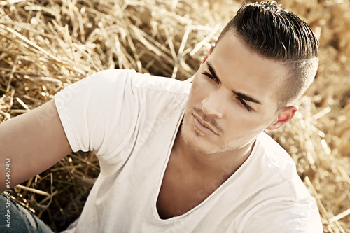 Portrait of  a beautiful young man outdoors in white casual shir