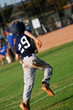 Teen baseball player running home