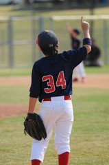 Youth ballplayer holding up finger.