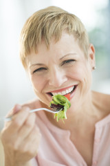 Closeup Of Happy Woman Eating Vegetable Salad