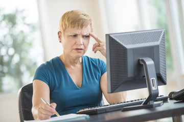 Tensed Businesswoman Working On Desktop PC