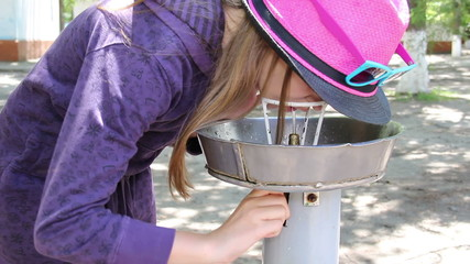 little girl drink the water at the drinking fountain