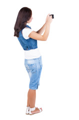Back view of woman photographing.