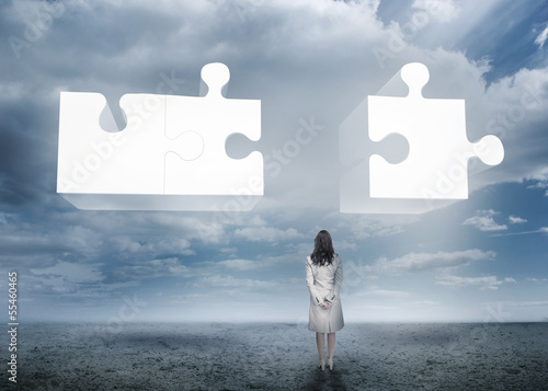 Businesswoman standing looking at jigsaw puzzle