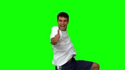 Handsome man giving thumbs up on green screen