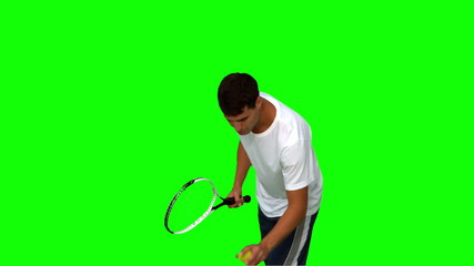 Man holding a tennis ball and a racquet on green screen