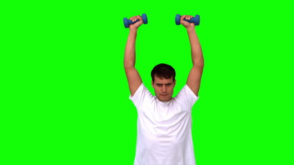 Man lifting dumbbells on green screen