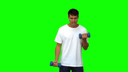 Handsome man lifting dumbbells on green screen