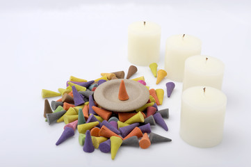 A pile of the incense cones with candle.