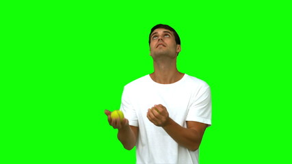 Handsome man dribbling with balls on green screen