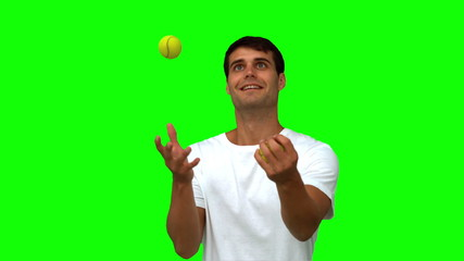Man dribbling with tennis balls on green screen