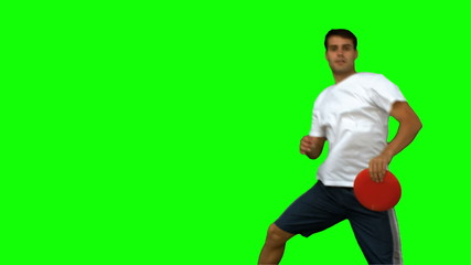 Man jumping and catching a frisbee on green screen