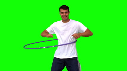 Man playing with a hula hoop on green screen