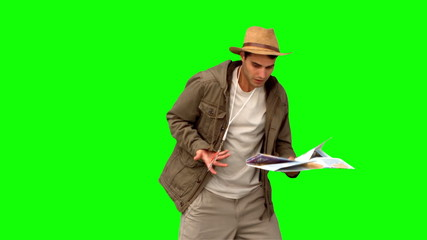 Man with a map and a compass orienteering on green screen