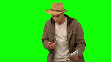 Man orienteering with a map and a compass on green screen