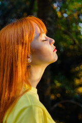 Red haired girl taking a deep breath relaxing with sunlight