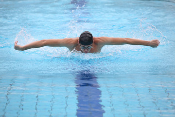 dynamic, fit swimmer breathing performing the butterfly stroke