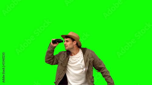 Man jumping and using binoculars on green screen