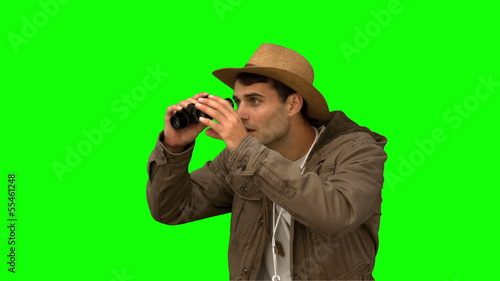 Man wearing a coat using binoculars on green screen