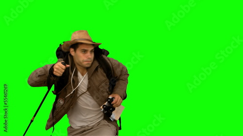 Man orienteering while holding a hiking stick on green screen