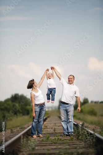 happy parents with baby on railroad