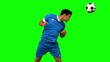 Attractive man heading a football on green screen