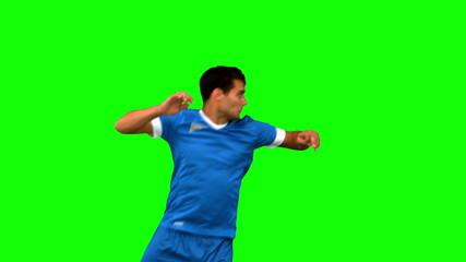 Handsome man heading a football on green screen